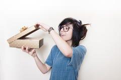 Ładnego młodej kobiety rozochoconego otwarcia prezenta złocista paczka Zdjęcie Royalty Free