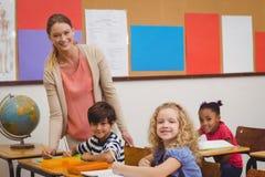 Ładnego nauczyciela pomaga uczeń ono uśmiecha się przy kamerą w sala lekcyjnej zdjęcie stock