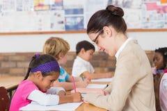 Ładnego nauczyciela pomaga uczeń w sala lekcyjnej obraz royalty free
