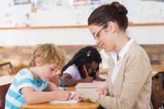 Ładnego nauczyciela pomaga uczeń w sala lekcyjnej obrazy royalty free