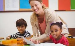 Ładnego nauczyciela pomaga uczeń w sala lekcyjnej Fotografia Stock