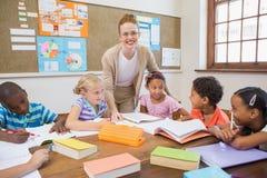 Ładnego nauczyciela pomaga ucznie w sala lekcyjnej zdjęcie stock