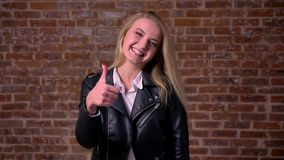 Ładnej blondynki caucasian kobieta w czarnej kurtce stoi prosto i pokazuje jak znak przy kamery ono uśmiecha się i chłodem