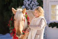 Ładnej blondynki kędzierzawy dziecko i uroczy konik z świątecznym wiankiem blisko małego drewnianego domu śnieżystych drzew i obraz stock
