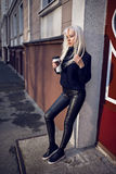 Ładnej blondynki wzorcowy pozować z kawą outdoors Obraz Royalty Free