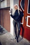 Ładnej blondynki wzorcowy pozować z kawowym outside Fotografia Stock