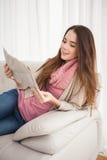 Ładnej brunetki czytelnicza gazeta na leżance Fotografia Stock