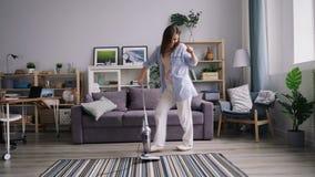 Ładnej gospodyni domowej czyści dywan z próżniowy czysty dancingowy śmiać się mieć zabawę zbiory
