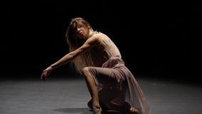 Ładnej kobiety dancingowy rówieśnik w ciemnym studiu przy światło reflektorów swobodny ruch zdjęcie wideo