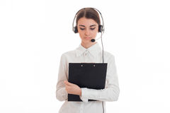 Ładnej młodej brunetki biznesowa kobieta z hełmofonami i mikrofon robimy notatkom odizolowywać na białym tle Fotografia Stock