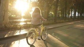 Ładnej małej dziewczynki jeździecki kolor żółty coloured rower na ulicie w lata miasta parku Drzewa i sunshines na tle zdjęcie wideo
