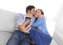 Ładni atrakcyjni potomstwa dobierają się obsiadanie w kanapy leżance bierze selfie fotografię z telefonem komórkowym wpólnie zdjęcie stock
