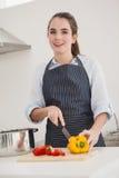 Ładni brunetki przecinania warzywa przy kontuarem Zdjęcia Stock