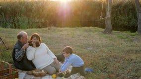 Ładni dzieci bawią się z jeżem na naturze blisko dziadka na tło zmierzchu i rzece zbiory