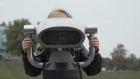 Ładni dziewczyn spojrzenia w teleskop w parku zbiory wideo