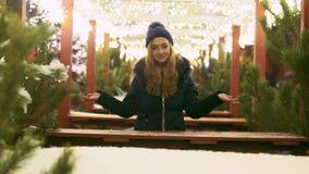 Ładni dziewczyna stojaki wśród sosen jarzy się z jaskrawymi światłami Bożenarodzeniowych gerlyands i Śliczna dama patrzeje cafee zdjęcie wideo