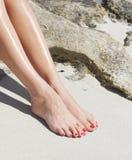 Ładni kobieta cieki z czerwonym pedicure'em: relaksować na piasku wakacje, obrazy royalty free