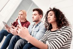Ładni młodzi ludzie używa ich gadżety zdjęcia stock