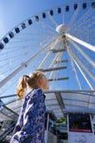 Ładni małych dziewczynek spojrzenia przy ferris kołem przeciw niebieskiemu niebu Obraz Royalty Free