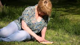 Ładni mody kobiety kłamstwa na zielonej trawie i czytaniu ciekawa książka w mieście parkuje przy letnim dniem zbiory wideo
