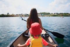 Ładni potomstwa macierzyści i mały berbecia syna kajakarstwo w jeziorze zdjęcie stock