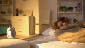 Ładny żeński patrzeje budzik blisko łóżka, dostaje opóźnioną pracę, ranku stres zdjęcie wideo