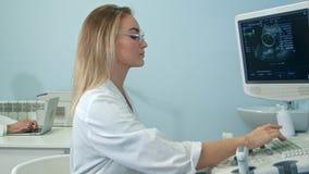 Ładny żeński sonographer pracuje przy ultradźwięku wyposażeniem Zdjęcie Stock