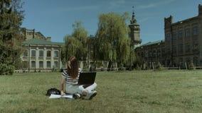 Ładny żeński uczeń pracuje na laptopie na gazonie zbiory