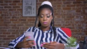 Ładny afrykański bizneswoman sprawdza numer karty kredytowej i pisze w puszku na jej smartphone