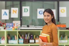 Ładny azjatykci nauczyciel ono uśmiecha się przy kamerą przy plecy sala lekcyjna przy szkołą podstawową Zdjęcia Royalty Free