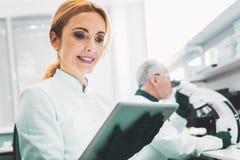 Ładny bioengineer ono uśmiecha się podczas gdy pracujący w firmie obrazy stock