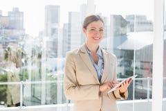 Ładny bizneswoman używa jej pastylka komputer osobistego i ono uśmiecha się przy kamerą Fotografia Royalty Free