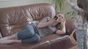Ładny blond kobiety lying on the beach na rzemiennej kanapie opowiada telefonem komórkowym Mała dziewczynka ciągnie jej macierzys zbiory wideo