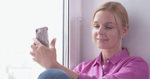 Ładny blondynki dziewczyny obsiadanie na smartphone w rękach i okno zbiory
