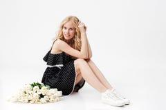 Ładny blondynki kobiety obsiadanie na podłoga z bukietem kwiaty obrazy royalty free
