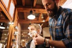 Ładny brodaty mężczyzna goli jego klienta Zdjęcia Stock