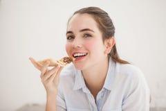 Ładny brunetki łasowania plasterek pizza Obraz Stock