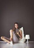 Ładny brunetki kobiety obsiadanie na podłoga z płaskim stołem i poduszką Obrazy Royalty Free