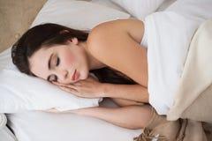 Ładny brunetki lying on the beach w łóżkowym dosypianiu Fotografia Royalty Free