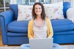 Ładny brunetki obsiadanie na podłoga i używać jej laptop Fotografia Stock