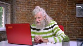 Ładny caucasian dziad używa czerwonego komputer i rozciąga jego ciało relaksować podczas gdy siedzący w czerwonej cegły studiu