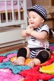 Ładny dziecko w pasiastej koszula i kapeluszach sadzających na macie w pokoju zdjęcia stock