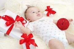 Ładny dziecko wiek 3 miesiąca kłama wśród prezentów Zdjęcia Royalty Free