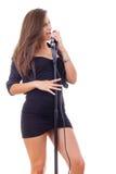 Ładny dziewczyna śpiew na mikrofonie w czerni sukni Zdjęcie Royalty Free