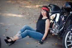 Ładny dziewczyna rowerzysta lub śliczna kobieta z siedzi na podłodze przy motocyklem eleganckimi, długie włosy jest ubranym cajga obraz stock