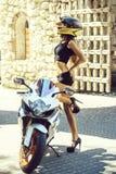 Ładny dziewczyna rowerzysta w motocyklu hełmie przy motocyklem lub hulajnoga obrazy royalty free