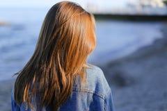 Ładny dziewczyna turysta en który stoi na seashore i rozwija włosy, Zdjęcie Royalty Free