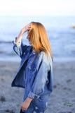 Ładny dziewczyna turysta en który stoi na seashore i rozwija włosy, Zdjęcie Stock