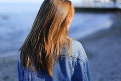 Ładny dziewczyna turysta en który stoi na seashore i rozwija włosy, Fotografia Royalty Free