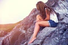 Ładny dziewczyny miejsca siedzące na kamieniu Zmierzch przy morzem Zdjęcie Stock
